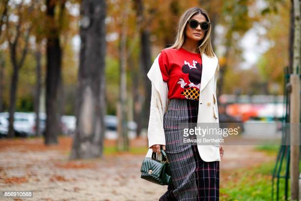 Thassia Naves wears a white coat a red top tartan skirt white shoes outside Leonard during Paris Fashion Week Womenswear Spring/Summer 2018 on...