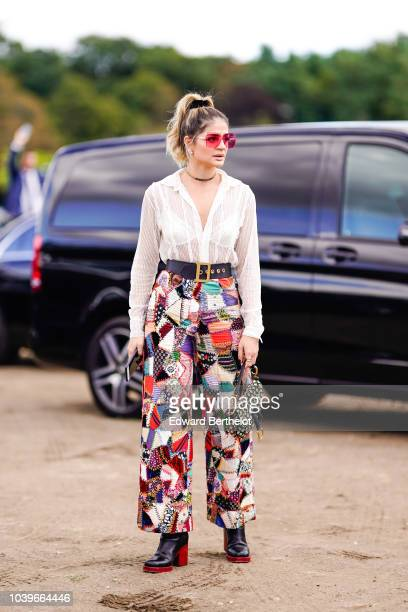 Thassia Naves wears a white lace mesh shirt patchwork multicolor printed pants black leather boots with red heels a Dior Saddle bag pink sunglasses...