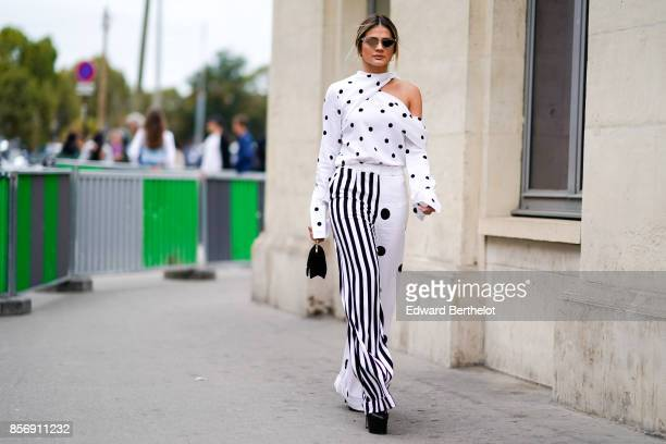 Thassia Naves wears an off shoulder white top black and white striped pants outside Giambattista Valli during Paris Fashion Week Womenswear...