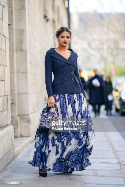 Thassia Naves wears earrings a navyblue vneck jacket a white and blue print long pleated skirt a Dior embroidered bag outside Dior during Paris...