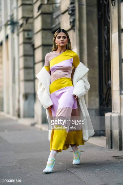 Thassia Naves wears earrings, a yellow and mauve striped flowing dress with mauve mesh inserts, a fluffy white coat, glittering sequined colorful...