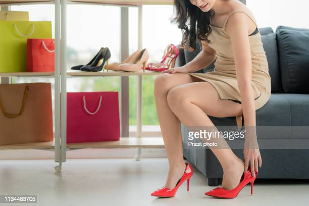 that is perfect pair! beautiful young woman trying on high heel shoes while sitting on sofa at the shoe store - サンダル ストックフォトと画像