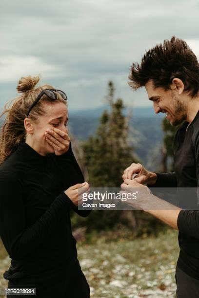 that moment when he proposes on a mountain top and she's overwhelmed - prometido relación humana fotografías e imágenes de stock
