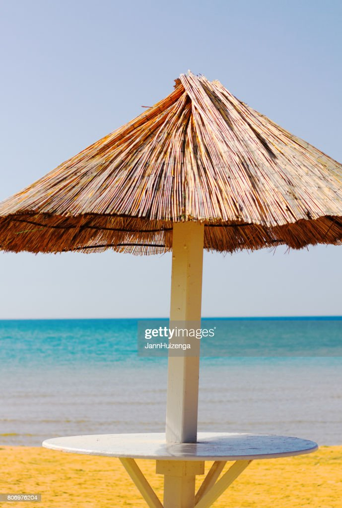 Thatched Beach Umbrella Golden Sand And Seascape At Dawn Stock Photo