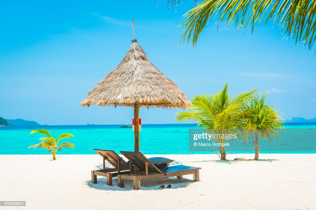Thatched Beach Umbrella On Tropical Stock Photo