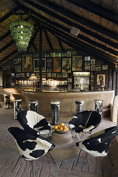 Thatched lapa styled bar with funky cowhide tub chairs. Planet Baobab, Botswana. (PR: Property Released)