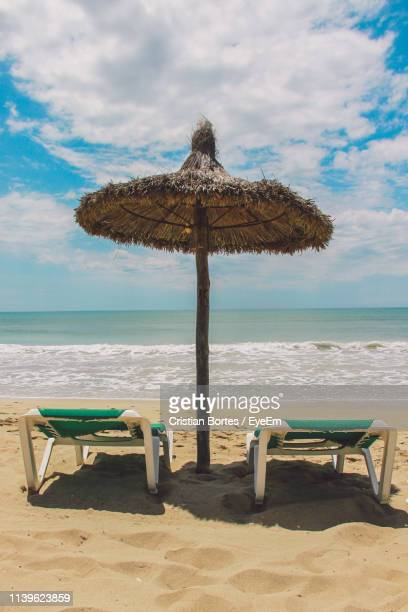 thatched parasol and lounge chairs on beach against cloudy sky - bortes stock pictures, royalty-free photos & images