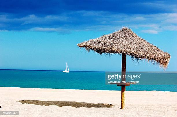 Thatched Roof At Beach Against Blue Sky