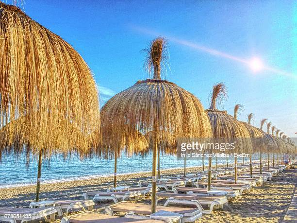 Thatched Roof Umbrellas With Lounge Chairs At Beach Against Blue Sky On Sunny Day