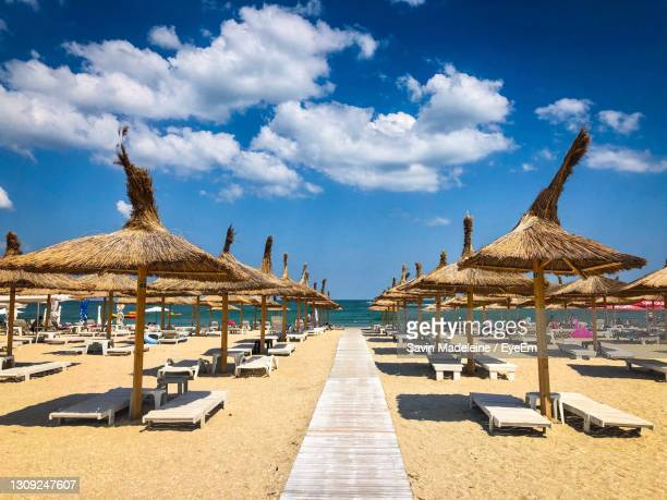 thatched roofs umbrellas and wooden sunbeds on the beach - romania stock pictures, royalty-free photos & images