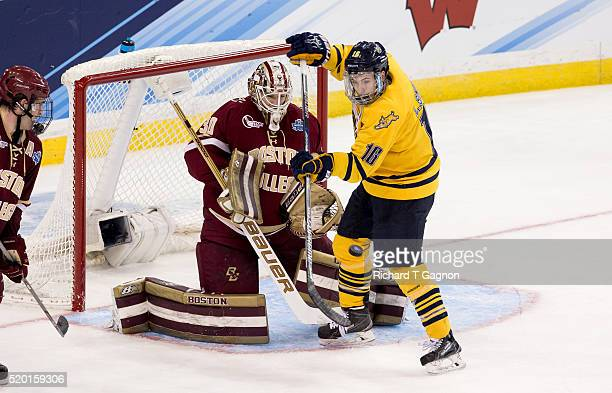 Thatcher Demko of the Boston College Eagles watches the puck as Landon Smith of the Quinnipiac University Bobcats tries to deflect it during game one...