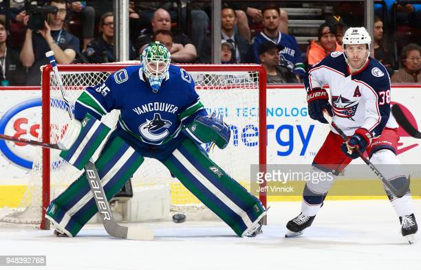Thatcher Demko of the Vancouver Canucks and Boone Jenner of the Columbus Blue Jackets watch a shot during their NHL game at Rogers Arena March 31...