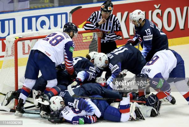 Thatcher Demko of United States is buried by a pack of players after stopping the puck during the 2019 IIHF Ice Hockey World Championship Slovakia...
