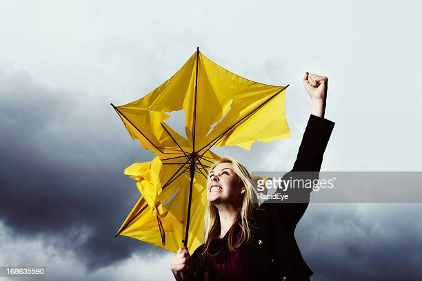 That's enough! Blonde with ruined umbrella shakes fist at thunderstorm