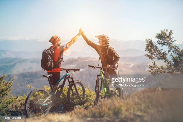 thats ride was awesome,  two mountain bikers on a mountain peak - mountain biking stock pictures, royalty-free photos & images