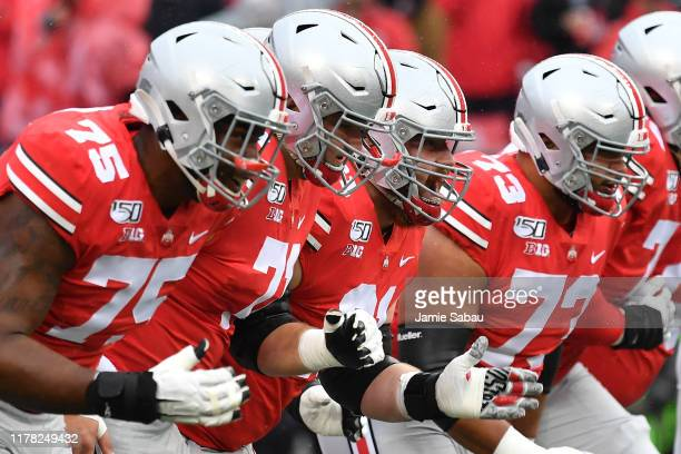 Thayer Munford Josh Myers Gavin Cupp and Jonah Jackson of the Ohio State Buckeyes warm up prior to game against the Wisconsin Badgers at Ohio Stadium...