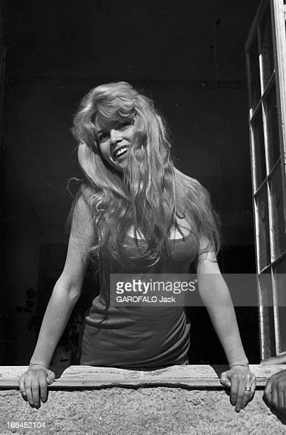 Brigitte Bardot Le 10ème Festival de Cannes 1957 se déroule du 2 au 17 mai attitude souriante de Brigitte BARDOT appuyée au rebord d'une fenêtre