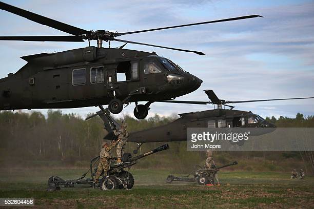 The 10th Mountain Division soldiers hook their 105mm Howitzers to Blackhawk helicopters while on a training mission for future deployments on May 18...