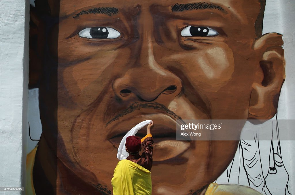 The 12th Gyalwang Drukpa, the Buddhist leader of South Asia (Nepal, India, Bhutan), waves a scarf in front of a mural of Freddie Gray as he tours the Sandtown neighborhood May 7, 2015 in Baltimore, Maryland. Gyalwang Drukpa was accompanied by the Rev. Jamal Bryant of the Empowerment Temple to tour the Baltimore neighborhoods affected by the recent unrest.