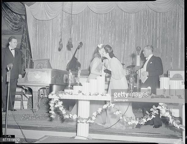 The 13th Annual Awards Dinner of the Academy of Motion Picture Arts and Sciences at the Biltmore Hotel. Actress Ginger Rogers receiving a kiss and...