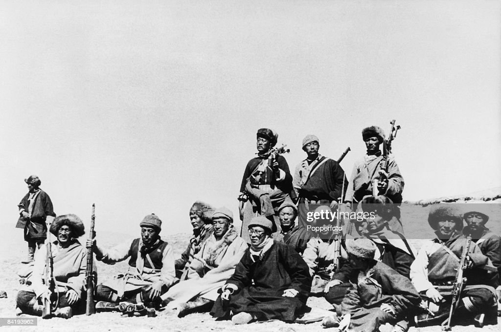The 14th Dalai Lama (sixth from left) flees from Tibet to India across the Himalayas, following a failed uprising against the Chinese occupation, 1959. Here he sits with his Khamba warrior guards during the journey.