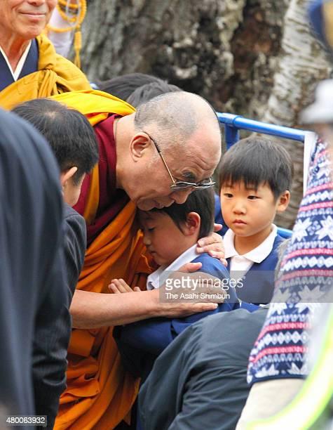 The 14th Dalai Lama hugs local residents as he visits the tsunami devastated Tokuho region at Saikoji Temple on November 5 2011 in Ishinomaki Miyagi...
