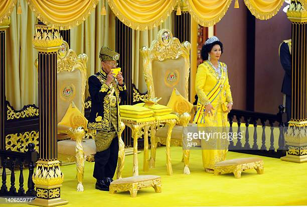 The 14th King of Malaysia King Abdul Halim Mu'adzam Shah kisses a copy of the Koran while Queen Haminah Hamidun looks on during the coronation at the...