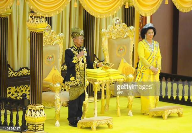 The 14th King of Malaysia King Abdul Halim Mu'adzam Shah lifts a ceremonial keris while Queen Haminah Hamidun looks on during the coronation at the...