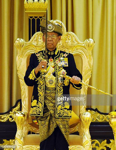The 14th King of Malaysia King Abdul Halim Mu'adzam Shah lifts a ceremonial keris during the coronation at the new National Palace in Jalan Duta...