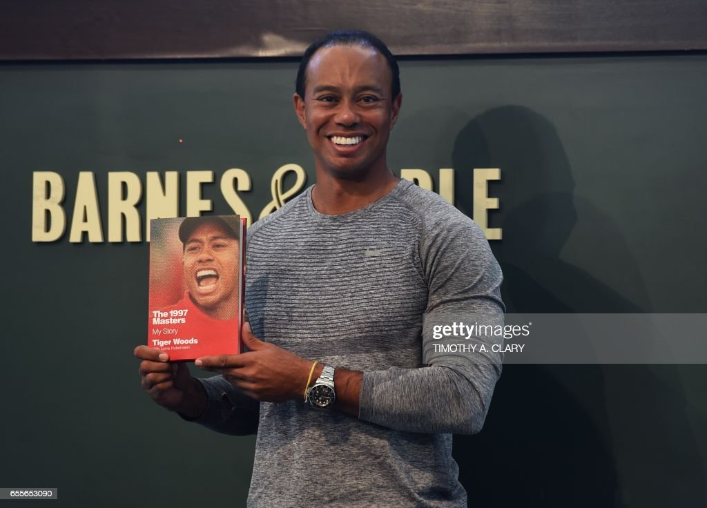 The 14-time major champ golfer Tiger Woods holds a copy of his new book 'The 1997 Masters: My Story' before his booking signing at Barnes & Noble's Union Square in New York on March 20, 2017. /