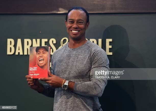 TOPSHOT The 14time major champ golfer Tiger Woods holds a copy of his new book The 1997 Masters My Story before his booking signing at Barnes Noble's...
