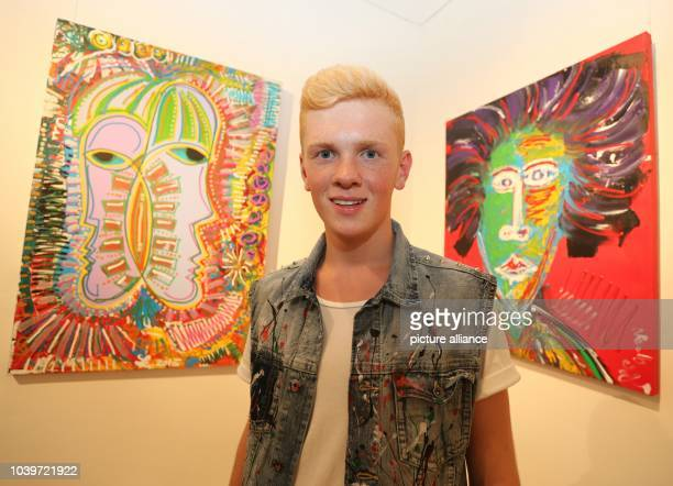 The 17year old painter Leon Loewentraut poses in front of his acrylic paintings 'Schirmkoepfe' and 'Grande Giorgio Leone' during his vernissage 'The...