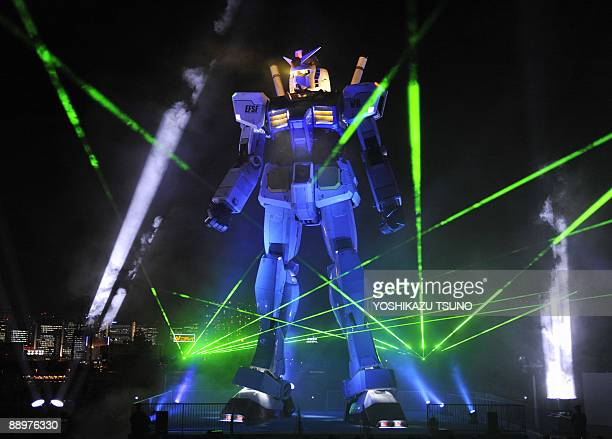 The 18metre tall statue of popular TV animation hero Gundam is lit up during the opening ceremony at a Tokyo park late on July 10 2009 The huge...