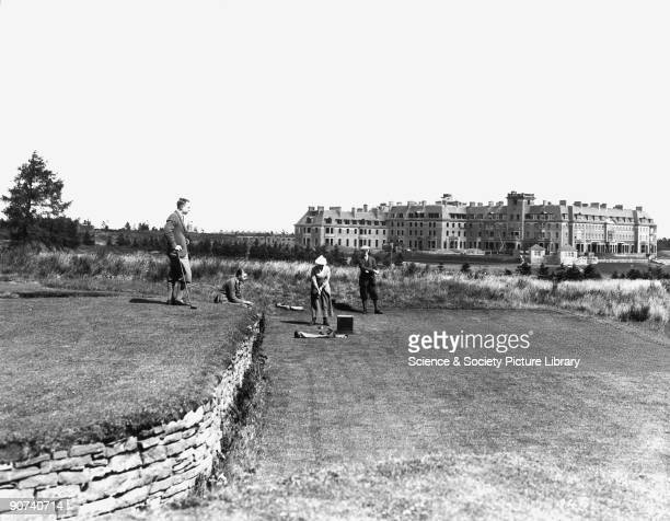 The 18th tee on the Queen's Golf Course, Gleneagles, Perth and Kinross, Scotland, 1923. A woman and three men play golf, against a backdrop of the...