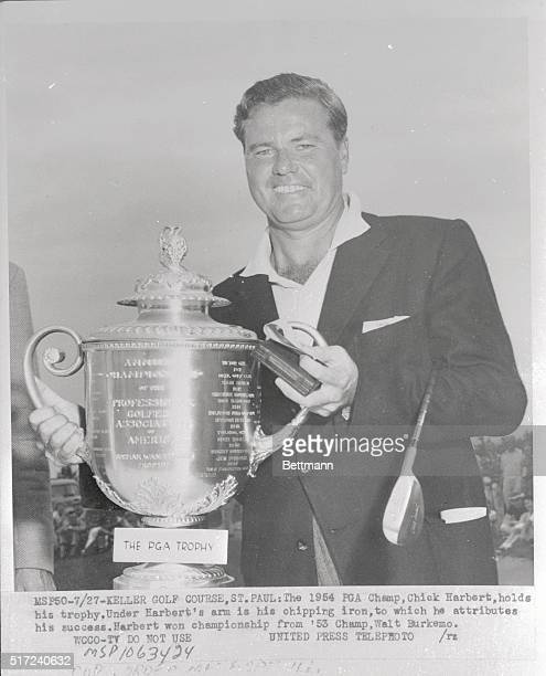 The 1954 PGA champion, Chick Harbert, smiles proudly as he holds the trophy he won by defeating Walt Burkemo in the contest at Keller Golf Course in...