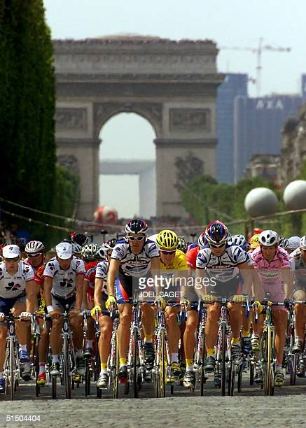 The 2000 Tour de France leader US Lance Armstrong rides with the pack on the 'Champs Elysees' past the 'Arc de Triompe' during the last stage of the...