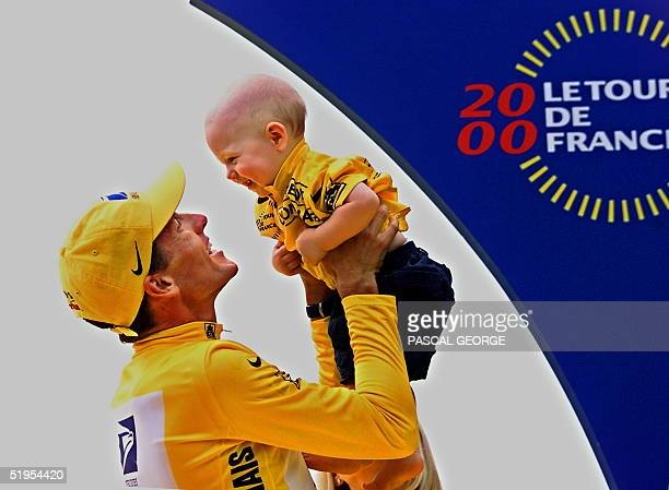The 2000 Tour de France winner US Lance Armstrong holds his son Luke in his arms on the podium of the last stage of the French cycling race on the...