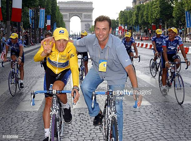 The 2002 Tour de France winner US Lance Armstrong rides with his sportive director Belgian Johan Bruyneel as he makes an honour lap on the 'Champs...