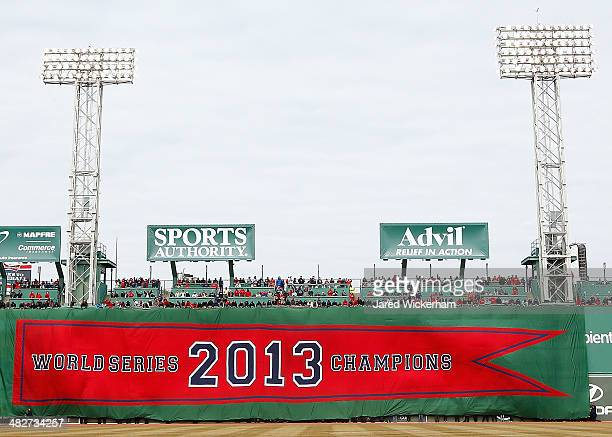 The 2013 World Series Champions Boston Red Sox banner is draped across the Green Monster prior to the Opening Day game between the Boston Red Sox and...
