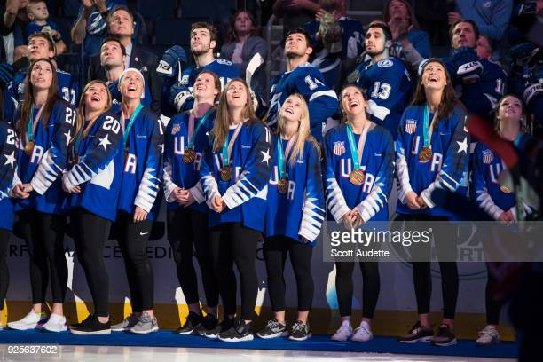 The 2018 US Olympic Women's Ice Hockey Team watch highlights from the Olympics as they are honored for winning gold before the game between the Tampa...