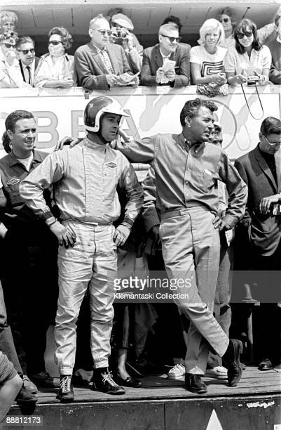 The 24 Hours of Le Mans Le Mans June 2021 1964 Carroll Shelby waits on the pit counter with driver Bob Bondurant for Bob's Cobra Daytona Coupe to pit...