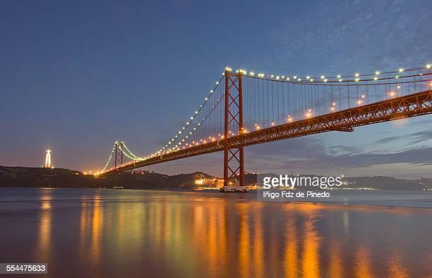 the  25 de abril bridge at dusk - statua di cristo re foto e immagini stock