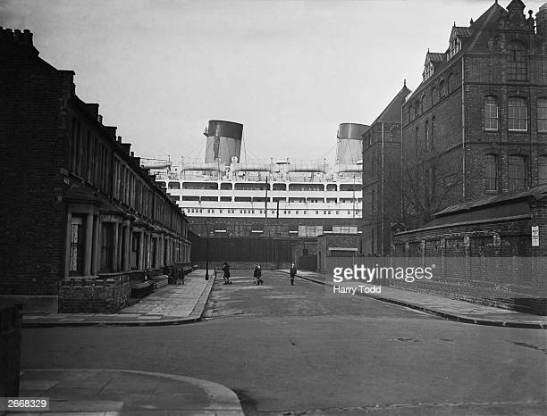 The 26263 ton Shaw Savill liner Dominion Monarch dwarfs the surrounding houses in Saville Road from her dry dock at the King George V docks in...