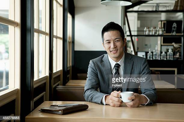 The 30th generation male businessman who drinks coffee