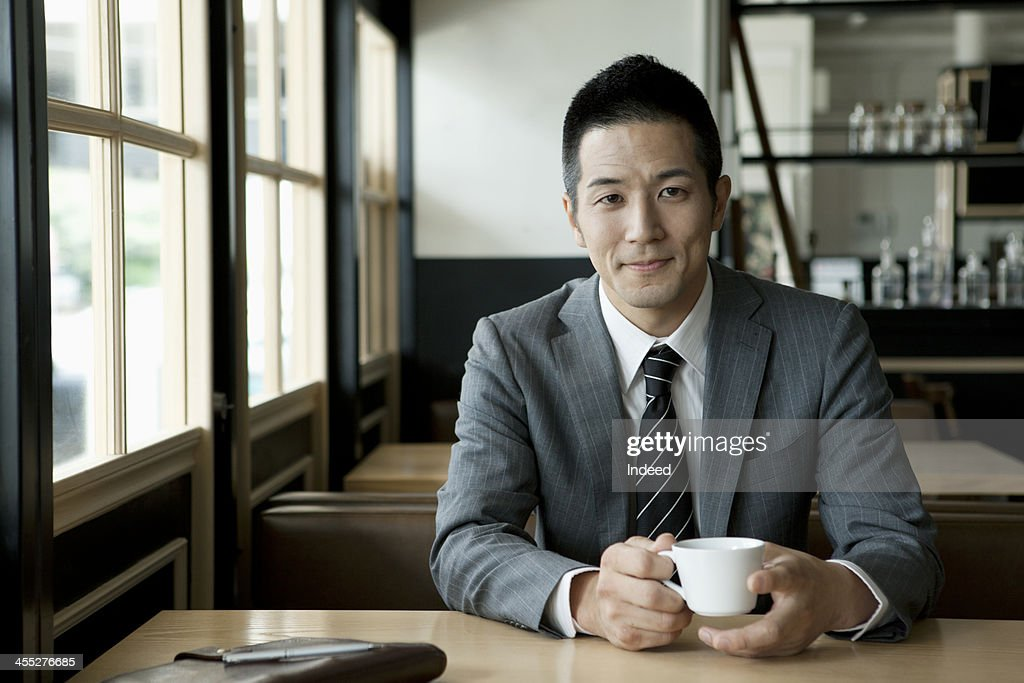 The 30th generation male businessman who drinks coffee : Stock Photo