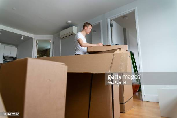 the 30-years-old man unpacking and assembling furniture in the living room of the recently purchased new apartment. - 25 29 years stock pictures, royalty-free photos & images