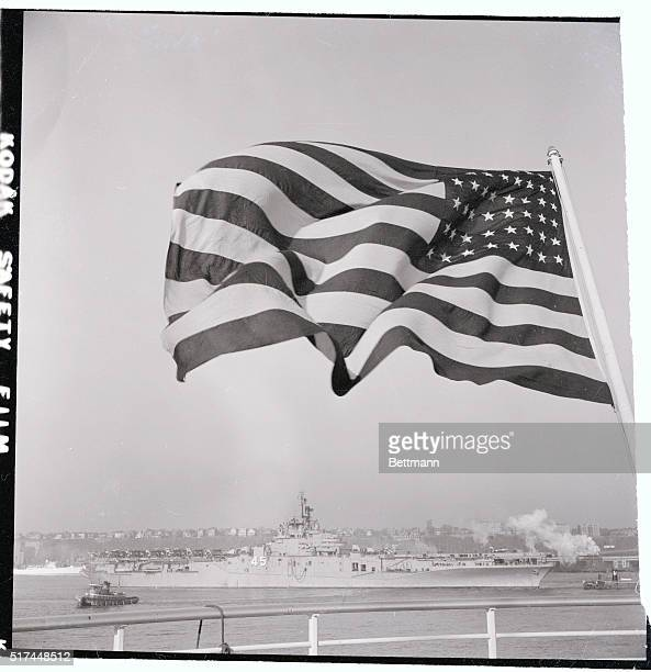 The 33000 ton US Navy carrier Valley Forge framed by the flag of the liner United States steams up New York's North River The carrier is in town to...