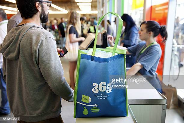 The 365 logo is displayed on a reusable shopping bag as customers check out on the opening day of the 365 by Whole Foods Market store in the Silver...