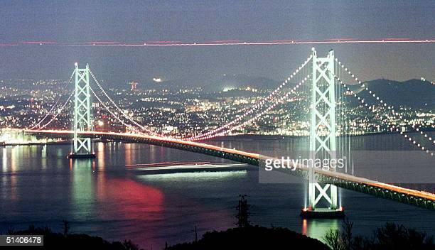 The 3911meterlong Akashi Kaikyo Bridge the world's longest suspension bridge is lighted up in the evening 05 April to mark its opening to traffic...