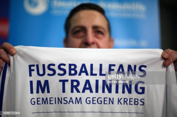 The 46-year-old participant Francesco Mattone holds up a jersey at a presentation introducing the new project 'Football Fans in Training' in the...